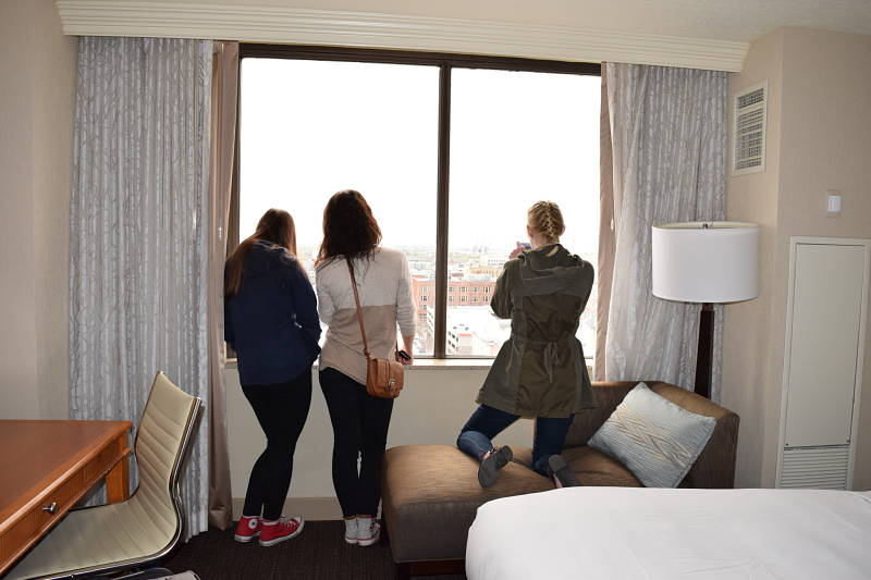 3 teen girls enjoying the view from a hotel dureing a birthday hotel staycation