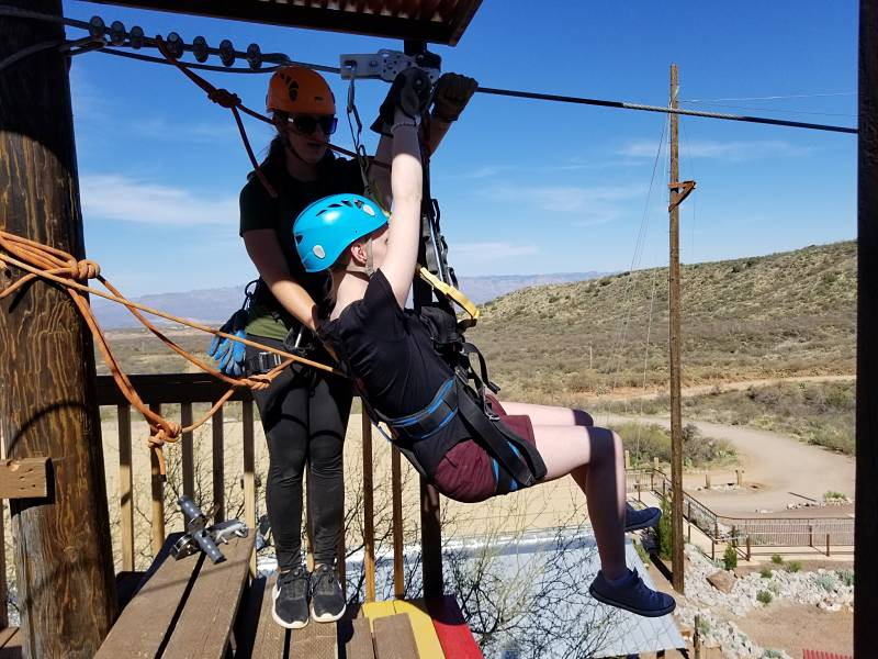 girl in zipline safety gear for a birthday adventure