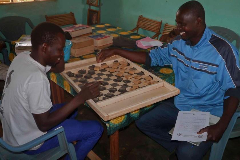 Alidou et un lecteur joue au damier