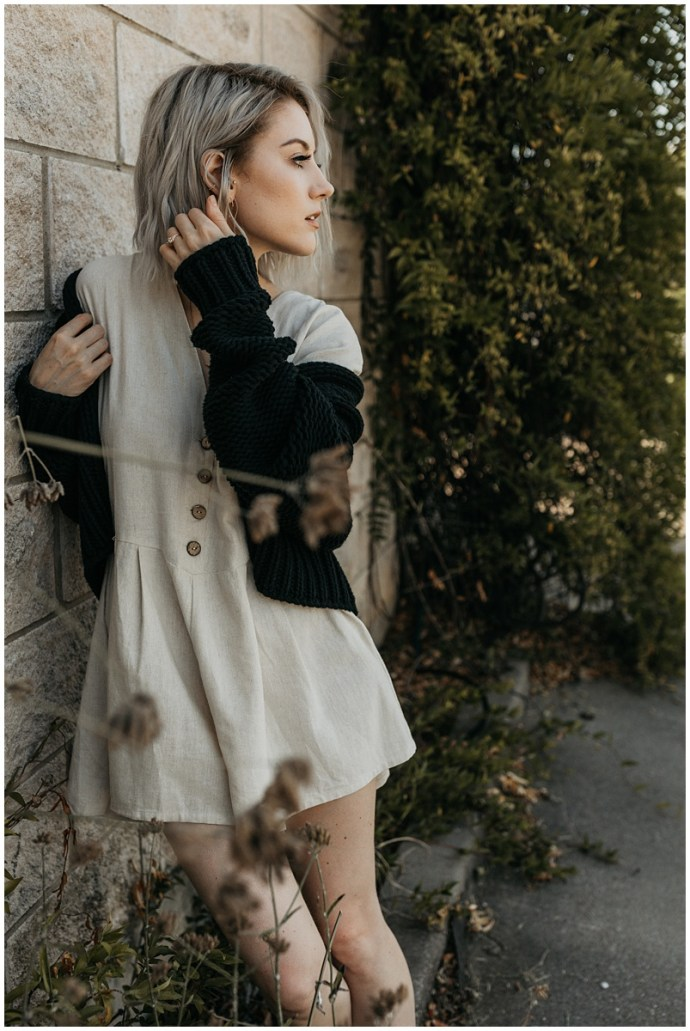 gorgeous young blonde woman wearing an off white shorts jumper and a black cardigan leans against a brick wall looking over at someone
