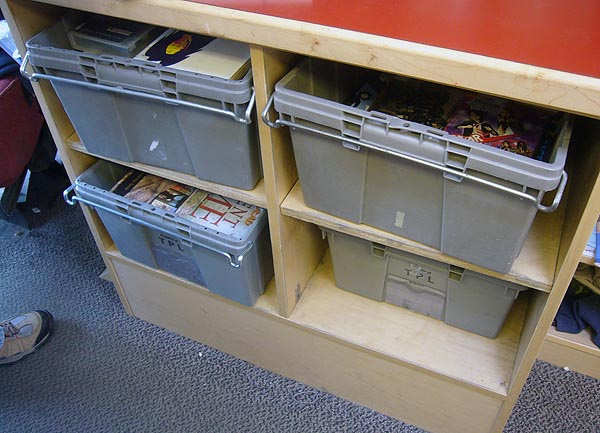 Four grey bins under a counter, all full of books