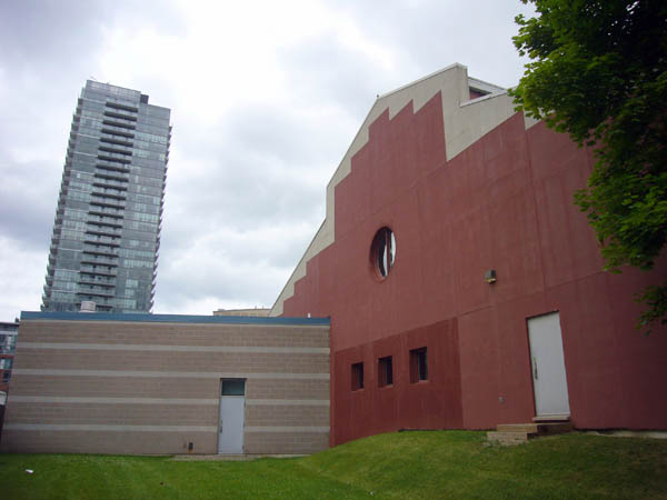 Barn-like end of building is clad in red brick with a white border and central porthole window. Alongside, a one-story beige addition. In the distance, a condo tower