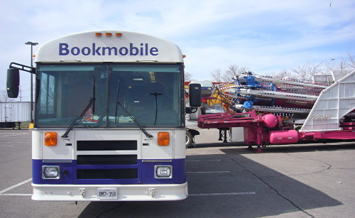 Front of Bookmobile bus next to the profile of large industrial apparatus folded onto a pink flatbed trailer