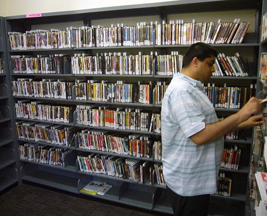 Wall shelves packed with DVDs, as man browses adjoining shelf