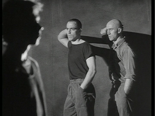 Two men lean, elbows on wall, facing the same direction, with another man blurred in foreground