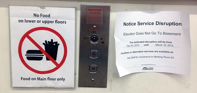 Frayed paper signs taped on either side of elevator buttons