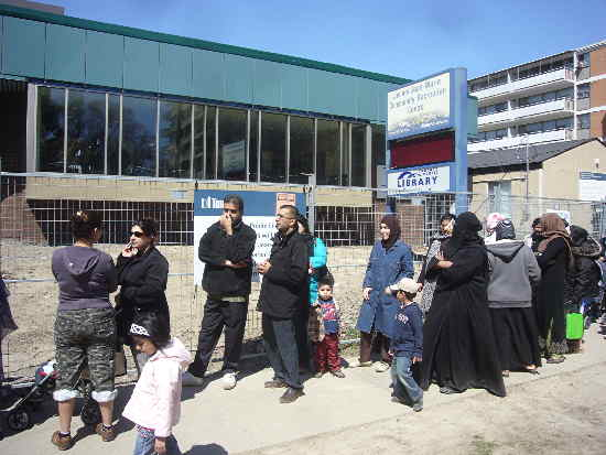 Queue of people outside community centre and library