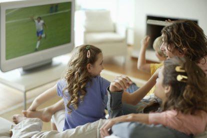 család a nappaliban tévénézés közben - közeleg a foci VB