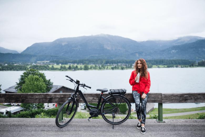 Piros kabátos lány elektromos kerékpárral a tóparton
