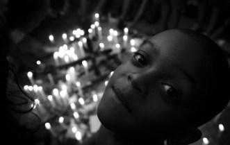 Menino em meio às velas que representam as mortes de moradores de diversas favelas de Niterói em protesto realizado em frente à prefeitura. Foto: Léo Lima / Favela em Foco