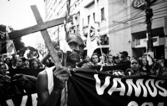 Homem segurando cruz durante manifestação de moradores das favelas atingidas pelas chuvas em Niterói. Para cobrar providências do governo local. Foto: Thiago Carminati/ Favela em Foco