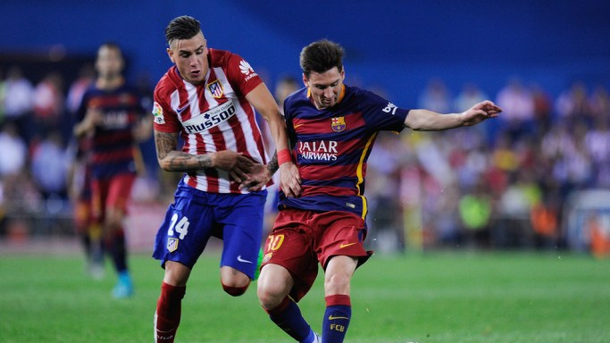MADRID, SPAIN - SEPTEMBER 12: Lionel Messi of FC Barcelona is fouled by Jose Maria Gimenez of Club Atletico de Madrid during the La Liga match between Club Atletico de Madrid and FC Barcelona at Vicente Calderon Stadium on September 12, 2015 in Madrid, Spain. (Photo by Denis Doyle/Getty Images)