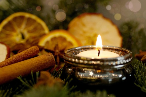 A single lit tealight sits among evergreen branches, cinnamon sticks, slices of orange, and star anise.