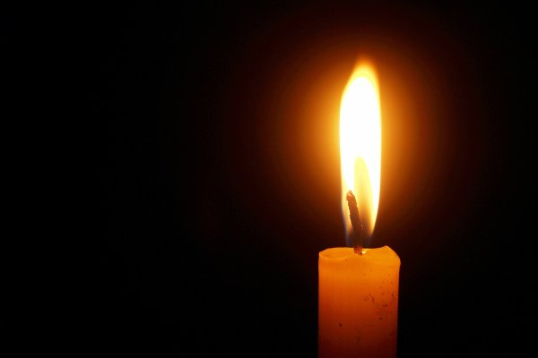 A single taper candle is lit against a dark background.