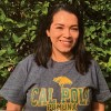 A smiling Liliana, with shoulder-length dark hair and a short-sleeve, gray, green, and yellow Cal Poly Pomona t-shirt, stands in front on a leafy green shrub.