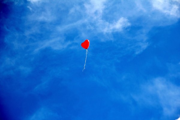 A single red heart-shaped balloon floats upwards through a bright blue sky with wispy white clouds.