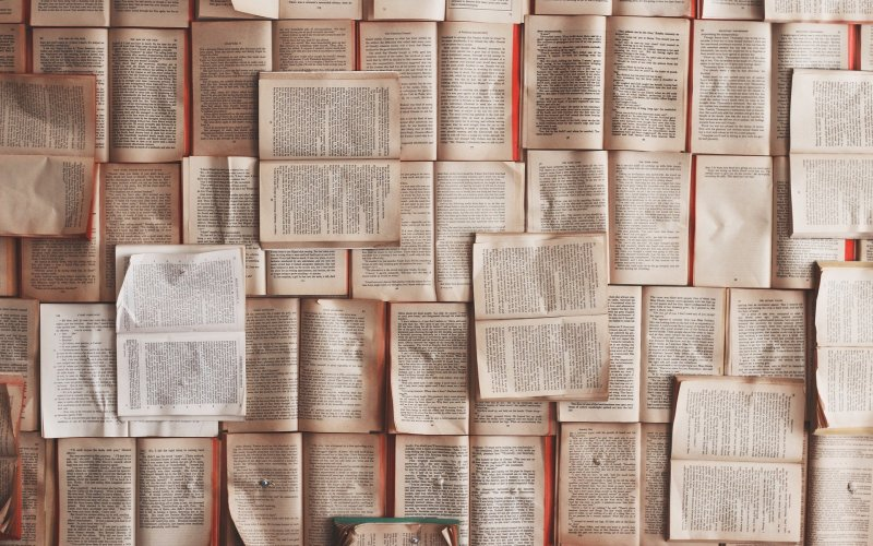 Pages of books are arranged at various angles, taking up the entire frame of the photo.