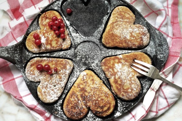 Five light brown pastries in the shape of hearts--two with raspberries on top--sit in a cast iron pan atop a red and white checked towel. A fork is poised to remove one of the pastries on the lower right side of the picture. Image via Pixabay.