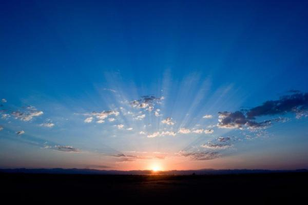A golden sun rises above the dark line of the horizon and casts rays of light as the blue, cloud-filled sky is illuminated pink and orange.
