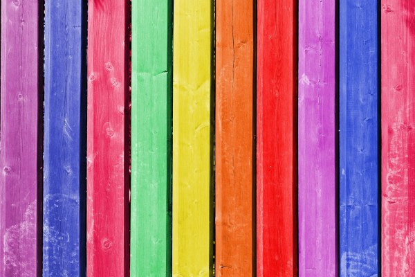 Vertical wooden slats are painted in numerous bright rainbow colors. From left to right: Purple, blue, pink, green, yellow, orange, red, purple, blue, pink. Image via Pixabay.