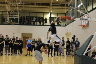 Senior Aidan Flanigan jumps over senior Samuel Yothers as he dunks the ball.