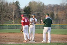 Junior Alex Lozado claps as he gets on first base.