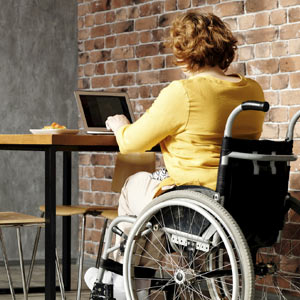 Woman in wheelchair working at a table