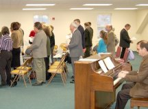 """A SLICE OF THE WORSHIPPERS attending a service organized by non-defectors from the Falls Church Episcopal Church in the spacious fellowship hall loft of the Falls Church Presbyterian is shown with volunteer pianist James Jelasic (right). City of Falls Church Mayor Robin Gardner, herself an Episcopalian, attended the service as a """"show of support"""" for the non-defectors. (News-Press photo)"""