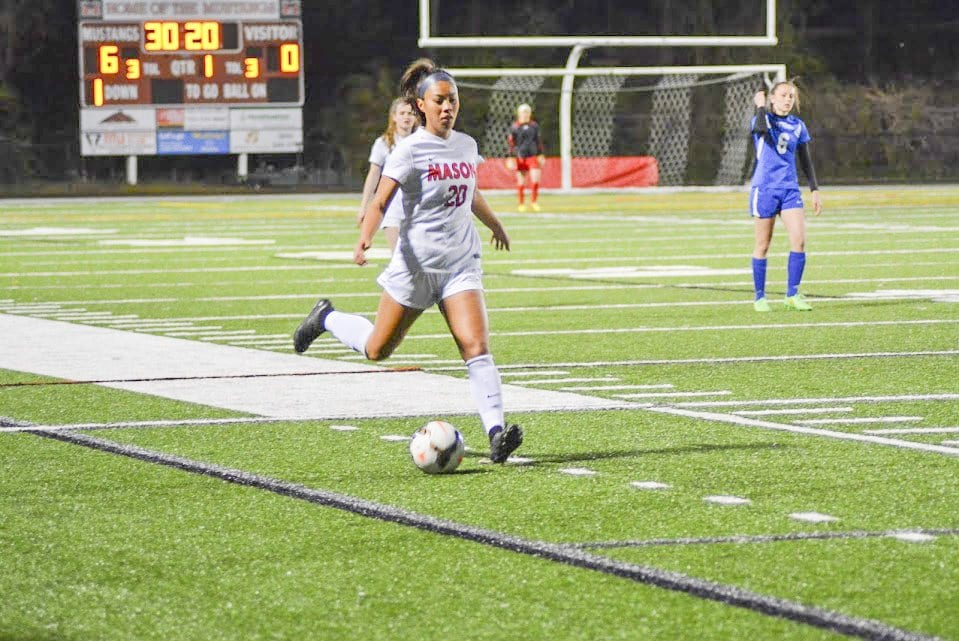 REBECCA CROUCH, junior midfielder on Mason's girls soccer team, prepares to kick the ball during a recent Mason win. She scored the Mustangs' last goal against Warren County High School during their 5-0 win over the Wildcats on Tuesday, April 26. (Photo: Carol Sly)