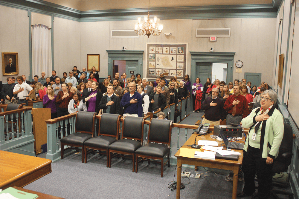 A 'STANDING ROOM ONLY' crowd of citizens, shown here during the Pledge of Allegiance at the start of the meeting, packed the City Council chambers at the Falls Church City Hall Monday night by far the most there to urge the Council to adopt its Fiscal Year 2014 budget with full funding of the School Board request. They got their way with a 5-2 vote. (Photo: News-Press)