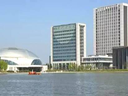 A spherical building and three rectangular tall buildings beside Ruyi Lake FCVAL Office exterior,
