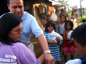 Evelyn Castillo and Dale Asis distributing food to street children in Tacloban City, Leyte Philippines