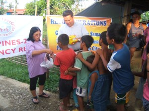 Evelyn Castillo and Dale Asis distributing food relief to street children in Barangay (Village) Santo Nino Tacloban City, Leyte Philippines