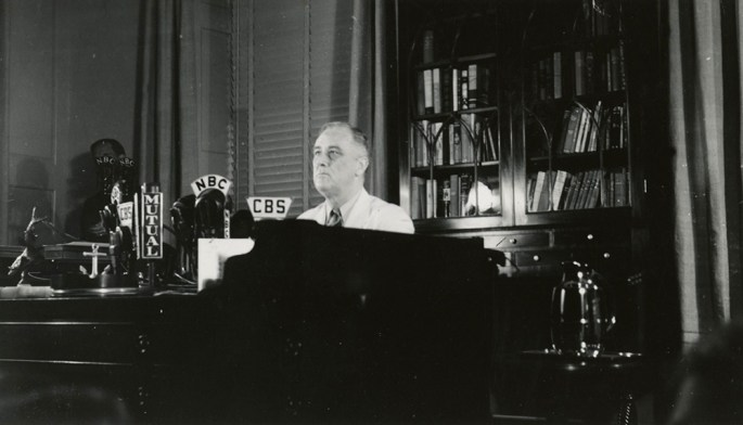 Photo showing FDR seated in his FDR Library study, microphones positioned on his desk