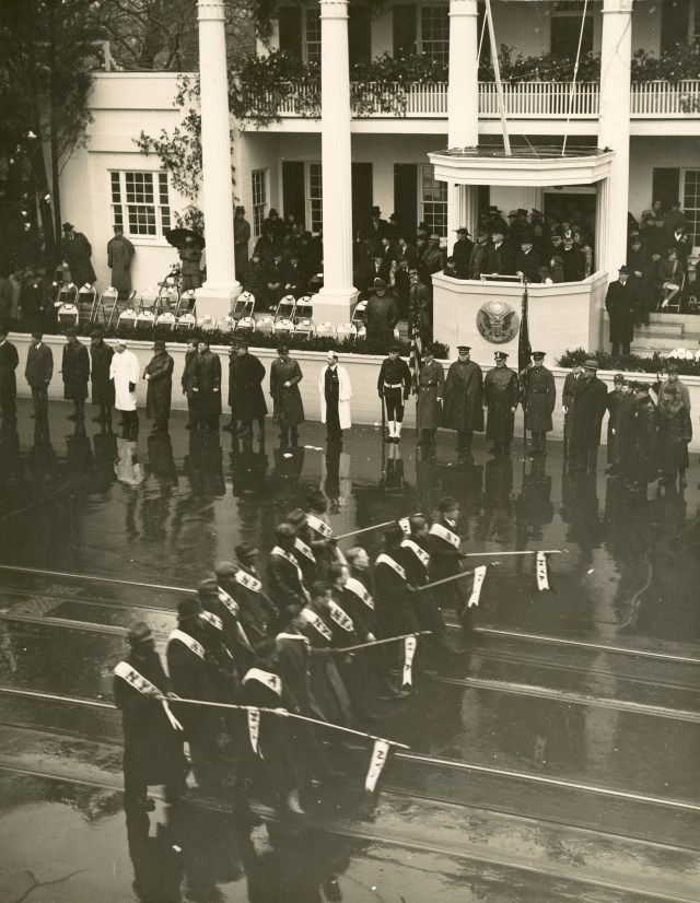 """President Roosevelt watching the Inaugural Parade from a replica of Andrew Jackson's """"Hermitage"""" in front of the White House.  January 20, 1937."""