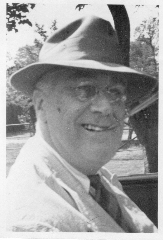 Black and white photo of FDR wearing a hat with a cigarette holder in his mouth