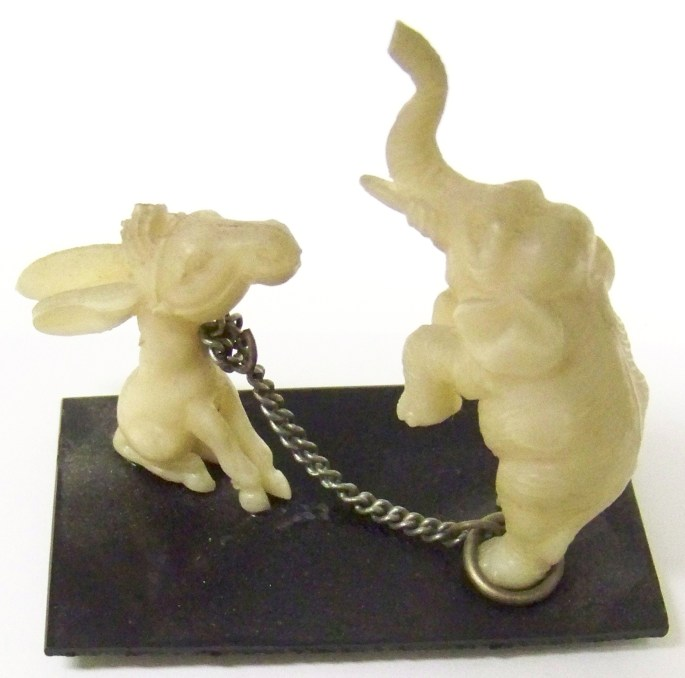 Figures of a white elephant chained to a white donkey