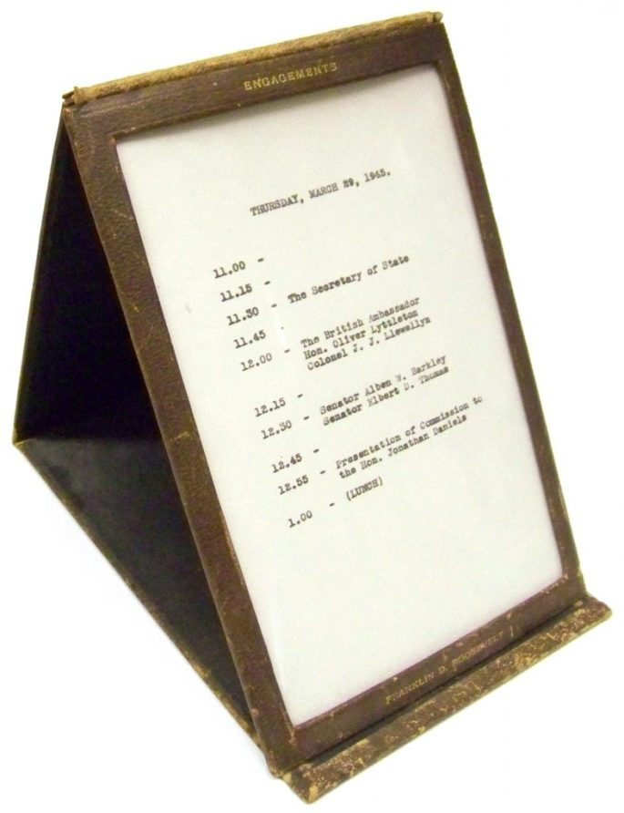 Angled view of a standing leather frame holding a schedule