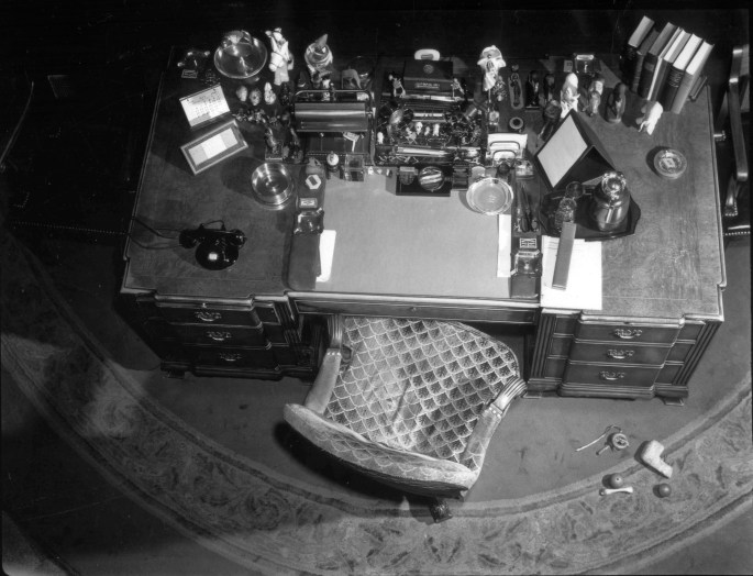 Black and white overhead view of a chair and desk with items clutter on top and dog toys on the floor