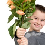 Eight years old boy presenting flowers, perhaps he is trying to say sorry or its Mothers Day