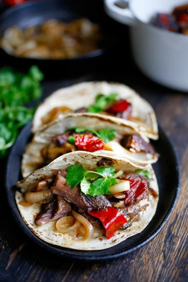 Tender, falling off the bone braised beef are the star of these Mexican short rib tacos, cooked low and slow in the oven with dried Mexican chilies, beef stock and stout.  | www.feastingathome.com