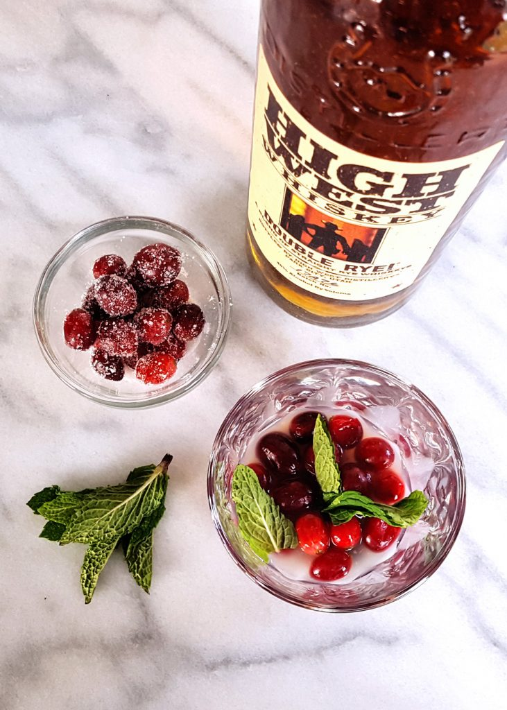 The Candied Cranberry Rye Whiskey Smash combines muddled mint leaves, tart fruit, and sparkling ginger beer with a spicy, high quality craft spirit in a lovely winter cocktail. | FeastInThyme.com