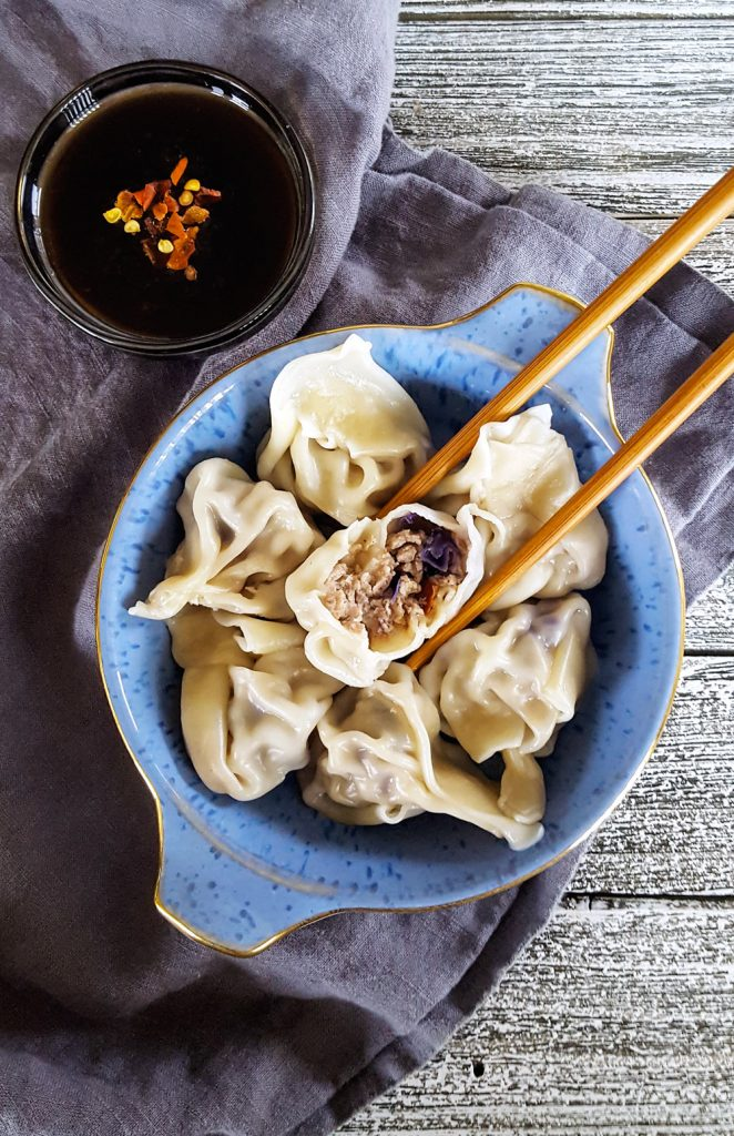 A ramekin of Simple Pork & Mushroom Dumplings, with one cut open and held with chopsticks so the filling can be seen.