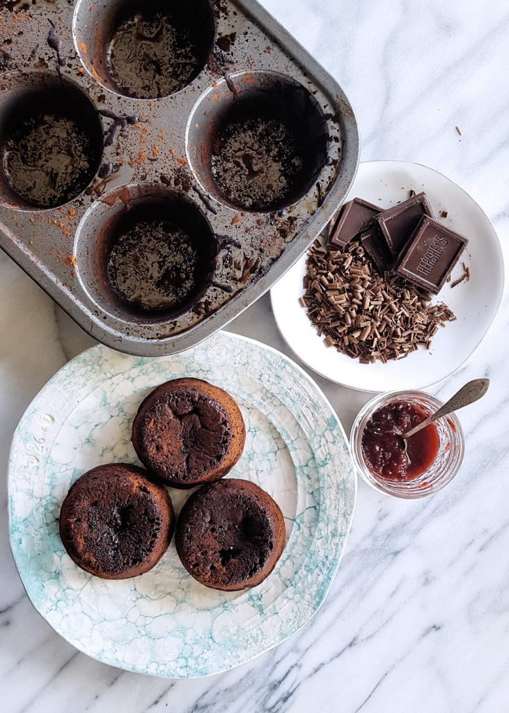 Three chocolate lava cakes on a plate, with an empty jumbo muffin tin, a jar of mixed berry jam, and a plate of chocolate shavings.