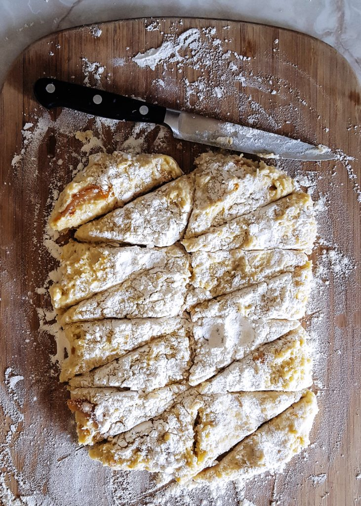 A rectangle of raw min orange scone dough sliced down the center, and then into sixteen triangles.
