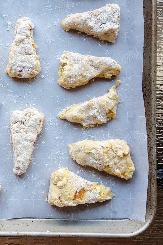 Raw triangles of mini orange scone dough spread out on a piece of parchment on a baking sheet.
