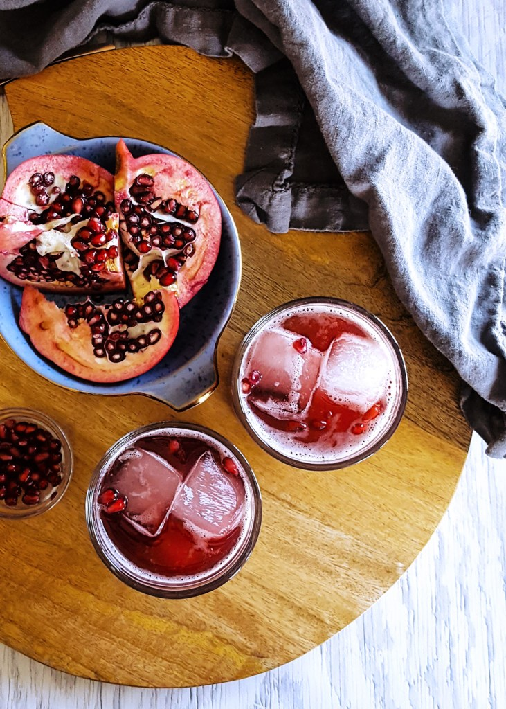 Two glasses of pomegranate bourbon cocktails on a circular wooden cutting board.