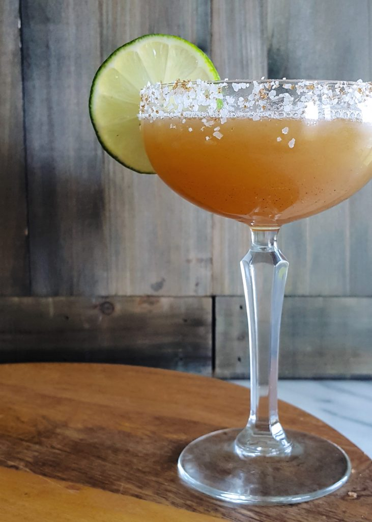 Desert Heat - a Spicy Margarita - in a coupe glass garnished with a lime.