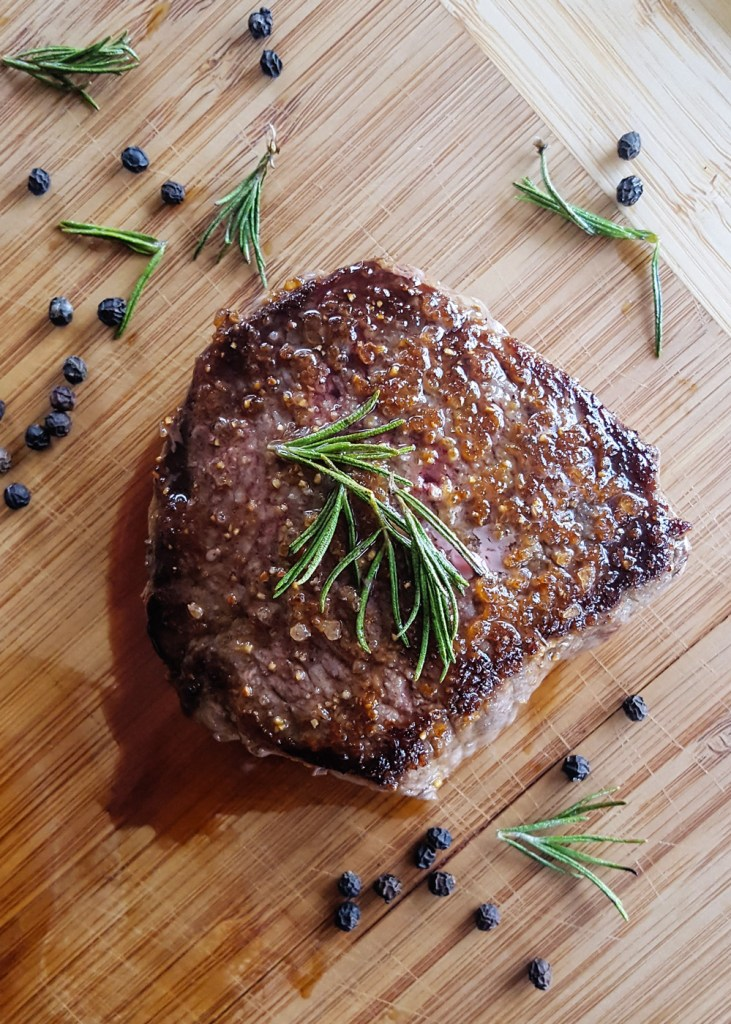 One pan seared steak tenderloin resting on a wooden cutting board. | FeastInThyme.com