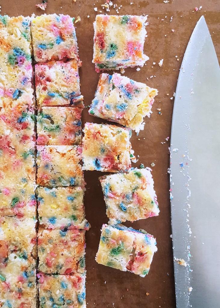 Funfetti Rainbow Cake cut into squares. | FeastInThyme.com